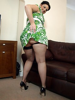 Cock-hungry suburban wife in green dress and fishnet stockings.
